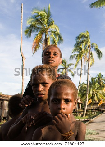 WEST PAPUA (IRIAN JAYA), ASMAT PROVINCE, INDONESIA - 19 JANUARY:  Daut, Yali, Den - Unidentified children of an  asmat tribe in a  small forest village on 19, january 2009 in West Papua, Indonesia. - stock photo