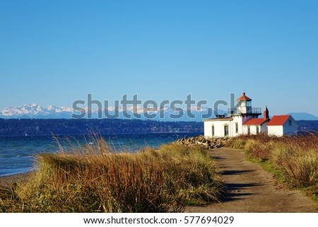 West Point Light is a lighthouse at Discovery Park in Seattle on Puget Sound's Elliott Bay. A hiking path leads to the lighthouse & beautiful view of snow capped Olympic Mountains on clear winter day.