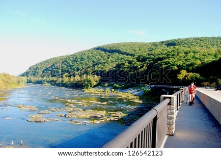 WEST VIRGINIA, USA - JULY 28: Hikers at Harpers Ferry Bridge on July 28, 2009 in WV, USA. Bridge is at famous Harpers Ferry historic town, many people hike the natural trails along Potomac River.