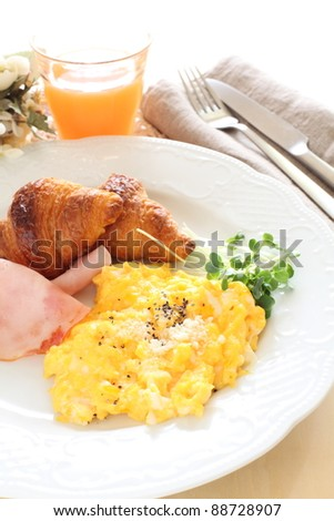 Western breakfast, scrambled egg and ham with croissants