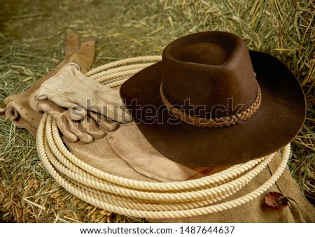 Western Cowboy hat with leather gloves, leather chaps and a roper's rope on hay in a barn
