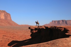Western Cowboy riding on Horse  from John Ford's Point overlook in Monument Valley Tribal Park with the mittens and Merrick Butte in Arizona, USA