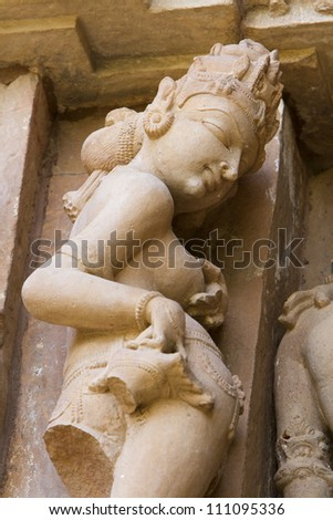 Western Group of temples of Khajuraho, woman picking a thorn from her foot - famous for their erotic sculptures, India.