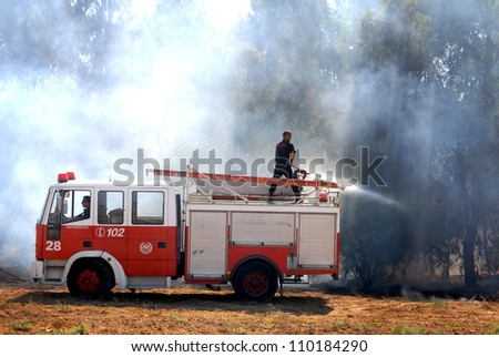 WESTERN NEGEV, ISRAEL - AUGUST 26: Firefighters on a fire engine try to control a bush fire on Sunday Aug 26 2007 in the Western Negev, Israel.