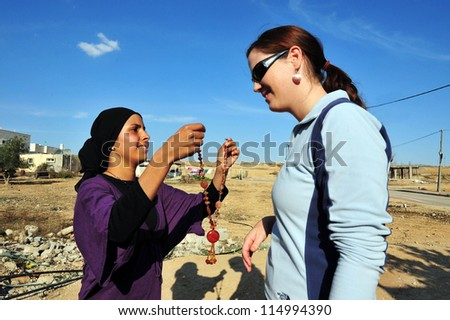 WESTERN NEGEV - NOVEMBER 26: A Bedouin woman gives a necklace to a visiting tourist as a welcome gift on November 26 2008. The nomadic Arabs live by rearing livestock in the deserts of southern Israel