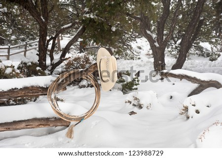 Western ranching equipment including a lasso and cowboy hat on a fence in the thick winter snow.