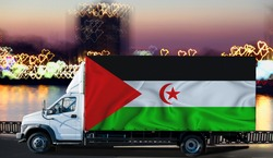 Western Sahara flag on the side of a white van against the backdrop of a blurred city and river. Logistics concept