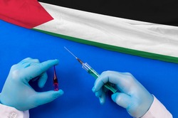 Western Sahara Vaccination. Hands of doctor holding syringe and coronavirus (COVID-19) vial vaccine on flag Western Sahara