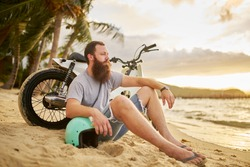 western tourist in thailand with beard sitting on beach with vintage motorbike