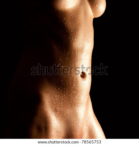 Wet abdomen of a nude young woman in front of black background
