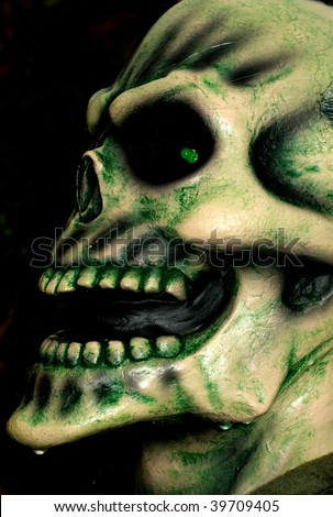 Wet and bony skeleton head of a zombie ready to grab someone on Halloween