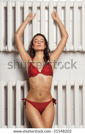 Wet and relaxed. A tanned pretty woman in red bikini standing in front of two lines of radiators.