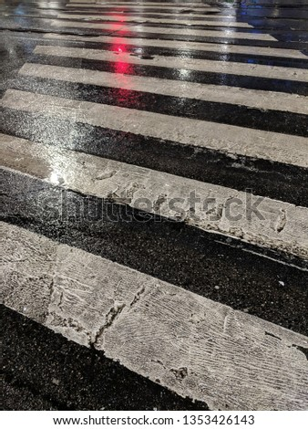 Wet asphalt and wet crossroad with red light.