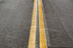 wet asphalt road with two yellow lanes