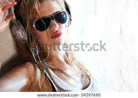 Wet babe in white shirt and sunglasses listening for the music using headphones