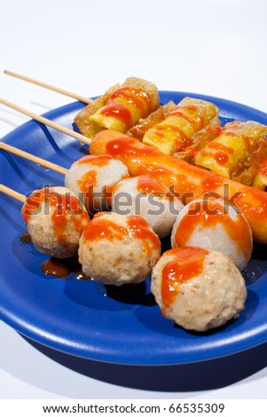 Wet ball grill skewers on the plate topped with spicy sauce placed on a plate. A white background. Blue needle plate. - stock photo