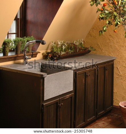 Wet bar by window, dark wood cabinets with slate sink and counter top.