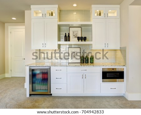 Wet bar with white cabinets fitted with a glass door beverage fridge, granite counter top featuring taupe subway tiles with a glossy finish. Northwest, USA #704942833