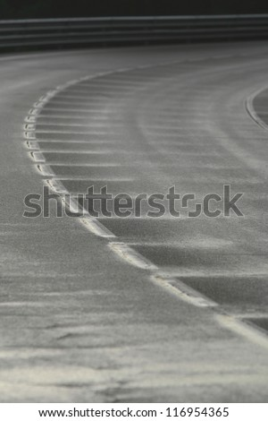 Wet bend in a road with a broken white line after the rain