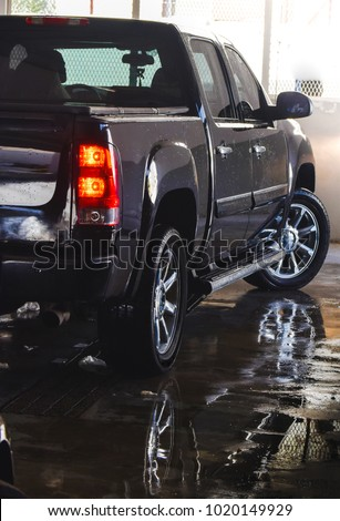Wet Black colored pickup truck after body wash in the Garage with red automotive tail light.