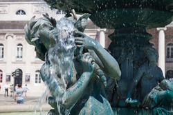 Wet bronze girl statue of fountain on the Rossio Square or Pedro IV Square, in Lisbon, Portugal. It was imported from France in the 19th century