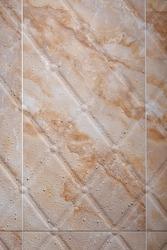 Wet brown marble textured tiles in the bathroom.