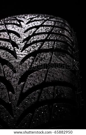 wet car tire on black background