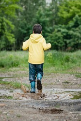 wet child jumping in puddle. Fun on street. Tempering in summer. Splashes, drops of water, outdoor. waterproof boots jump in puddle and mud in rain. Happy childhood