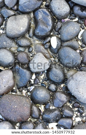 Wet cobble stones of varying sizes and shapes with some gravel among them.