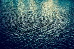 Wet cobblestone street at night