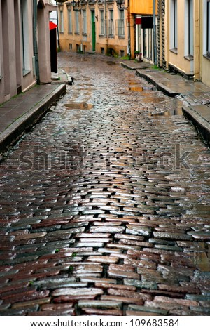 Wet cobblestones after rain on narrow street in the old town of Tallinn, Estonia