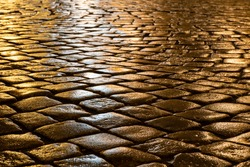 Wet cobblestones at night after rain on a street or road surface, bottom view