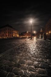 Wet cobblestones reflecting streetlight during autumn night. Stockholm, Sweden
