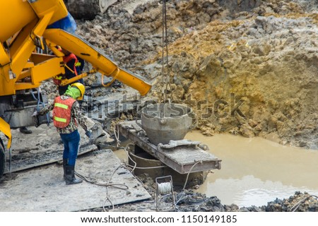 Wet concrete pour or pump from the concrete lorry into the bore pile casing. Bored piles are piles where the removal of spoil forms a hole for a reinforced concrete pile which is poured in situ.