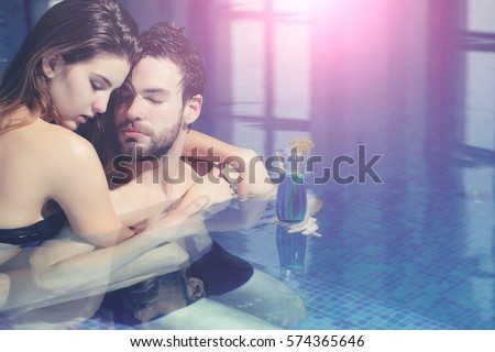 wet couple of pretty woman or sexy girl and handsome bearded man or guy with muscular body in swimming pool with blue water holds cocktail glass, copy space #574365646