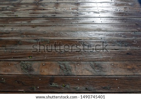 Wet, dark planks on a deck or veranda