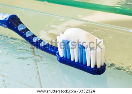 wet dental toothbrush with paste in bathroom