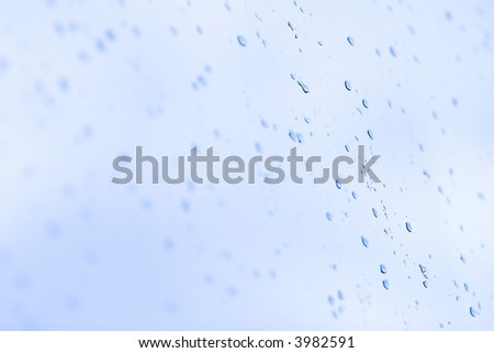 Wet drops on a glass. Blue tint and low dof. - stock photo