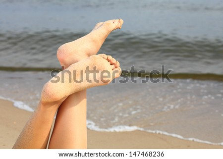 wet female feet on the beach and sand