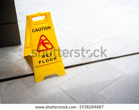 Wet floor caution sign on walkway near the building after raining. Warning yellow plastic caution wet floor sign on the ground with copy space.