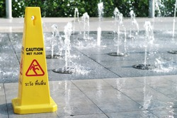 Wet floor caution sign. Warning symbol of slippy floor for pedestrian. Fountain makes wet floor. Thai language means caution wet floor.