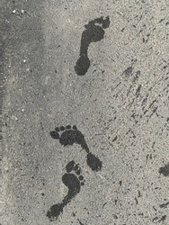 Wet foot print. Foot imprint on asphalt