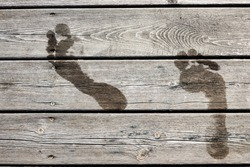 Wet footprints on a wooden jetty / bridge. Concept for swimming / bath, summer holidays / vacation, fun in the sun, etc. Fullscreen texture.