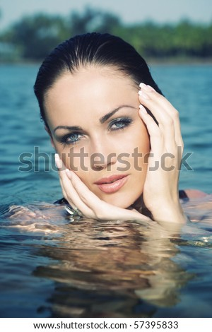 Wet head of the beautiful woman in the summer water. Artistic colors added