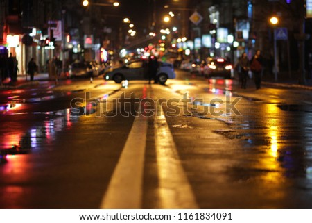 Wet highway at night with reflection of street lamps in puddles. Beautiful night cityscape. The center of the roadway is blocked by a police car.