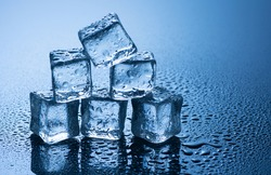 wet ice cubes on blue background with water drops