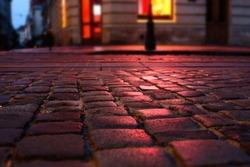 Wet illuminated by red light cobblestone street at night