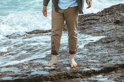 wet man legs in pants walking by sea rocky beach enjoying water. summer vacation