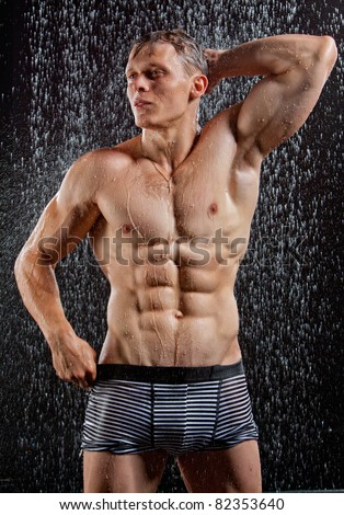 Wet muscle sexy young man posing under the rain in studio