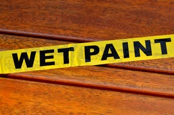 Wet paint sign on a wooden park bench